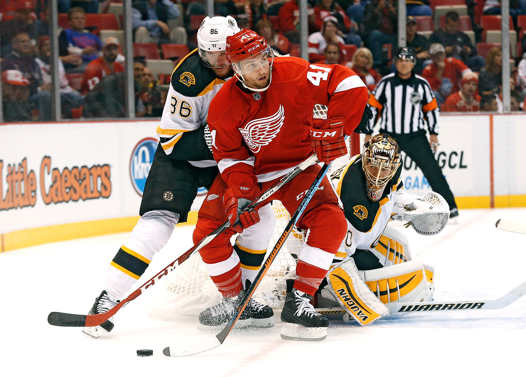 . Detroit Red Wings right wing Luke Glendening (41) tries to skate as Boston Bruins defenseman Kevan Miller (86) and Boston Bruins goalie Tuukka Rask (40), of Finland, defend in the second period of a NHL hockey game in Detroit Thursday, Oct. 9, 2014. (AP Photo/Paul Sancya)