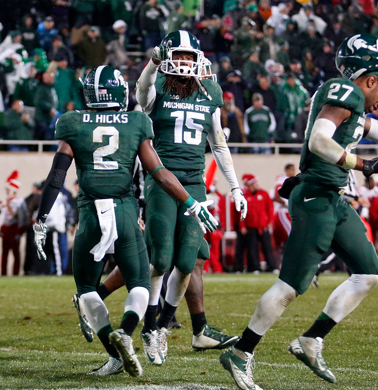 . Michigan State\'s Trae Waynes (15) celebrates his interception with Darian Hicks (2) and Kurtis Drummond with less than a minute remaining in the fourth quarter of an NCAA college football game against Nebraska, Saturday, Oct. 4, 2014, in East Lansing, Mich. Michigan State won 27-22. (AP Photo/Al Goldis)