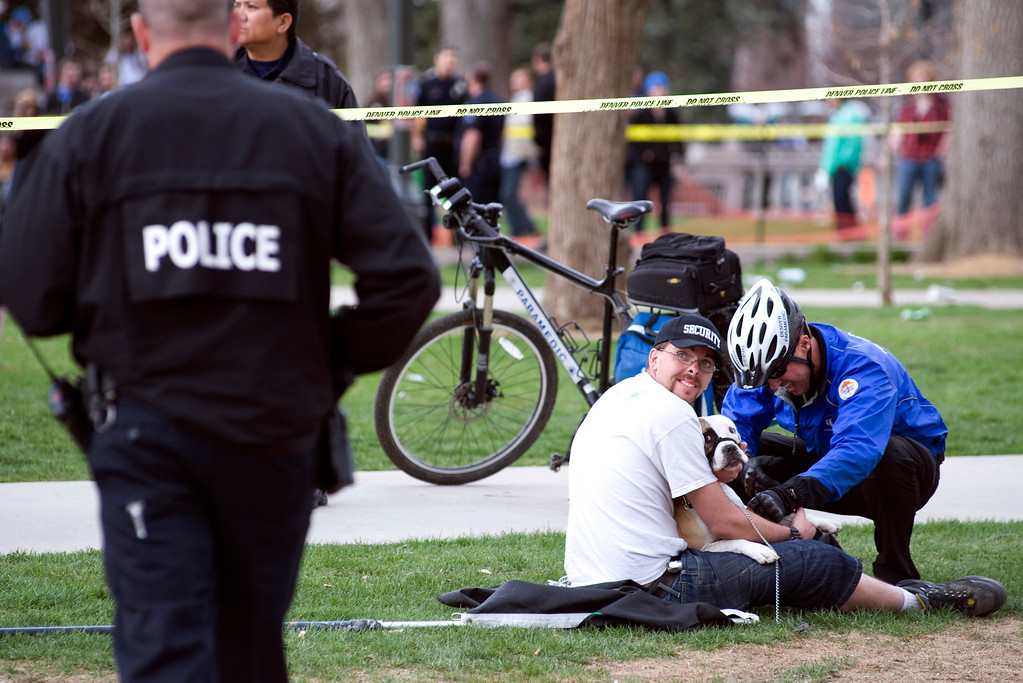 . Denver, CO. - April 20: A Denver Paramedic attends to a dog that was grazed by a bullet as the dogs owner holds it after a 4/20 pot rally at Denver\'s Civic Center Park, April 20th, 2013. Two people were shot during Saturday\'s annual 4/20 marijuana rally, held on a day cannabis enthusiasts regard as a holiday called 4/20 drew tens of thousands to Denver\'s Civic Center park. This is the first 4/20 marijuana rally since Colorado voters legalized marijuana use for people 21 and older in November. (Photo By Kholood Eid/Special to The Denver Post)