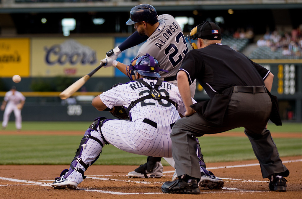 . Yonder Alonso #23 of the San Diego Padres hits an RBI single during the first inning as catcher Wilin Rosario #20 of the Colorado Rockies looks on at Coors Field on August 13, 2013 in Denver, Colorado.  (Photo by Justin Edmonds/Getty Images)