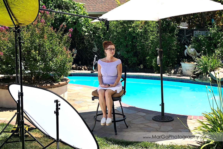 behind the scenes of outdoor filming woman speaker in lavender top