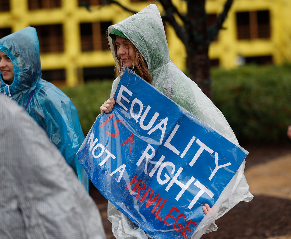 . A woman makes her way through a heavy downpour to a protest march Saturday, Jan. 21, 2017, in Atlanta. Thousands of people marched through Atlanta one day after President Donald Trump\'s inauguration. (AP Photo/John Bazemore)
