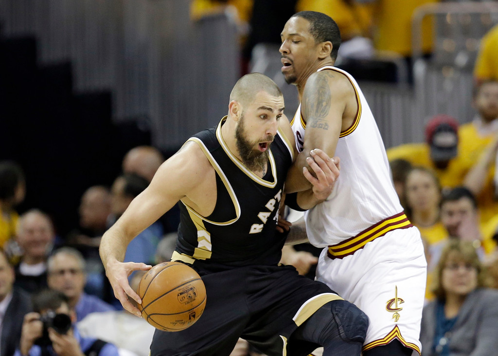 . Toronto Raptors\' Jonas Valanciunas, left, from Lithuania, drives past Cleveland Cavaliers\' Channing Frye during the first half in Game 2 of a second-round NBA basketball playoff series, Wednesday, May 3, 2017, in Cleveland. (AP Photo/Tony Dejak)