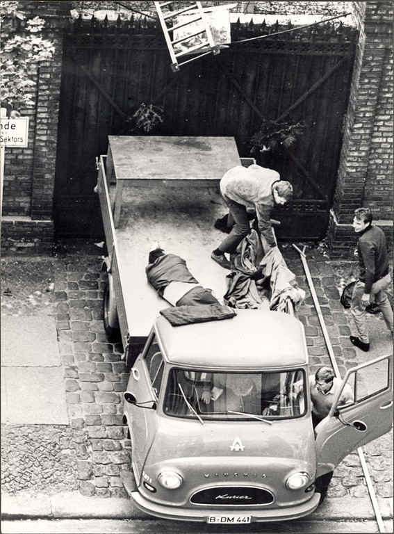 . High-angle shot of Stanislaus Gefroerer laying in the back of a lorry after crossing the Berlin Wall by ladder, fearing that guards may have seen him escape, Berlin, West Germany, September 20, 1965.  (Photo by Express Newspapers/Getty Images)