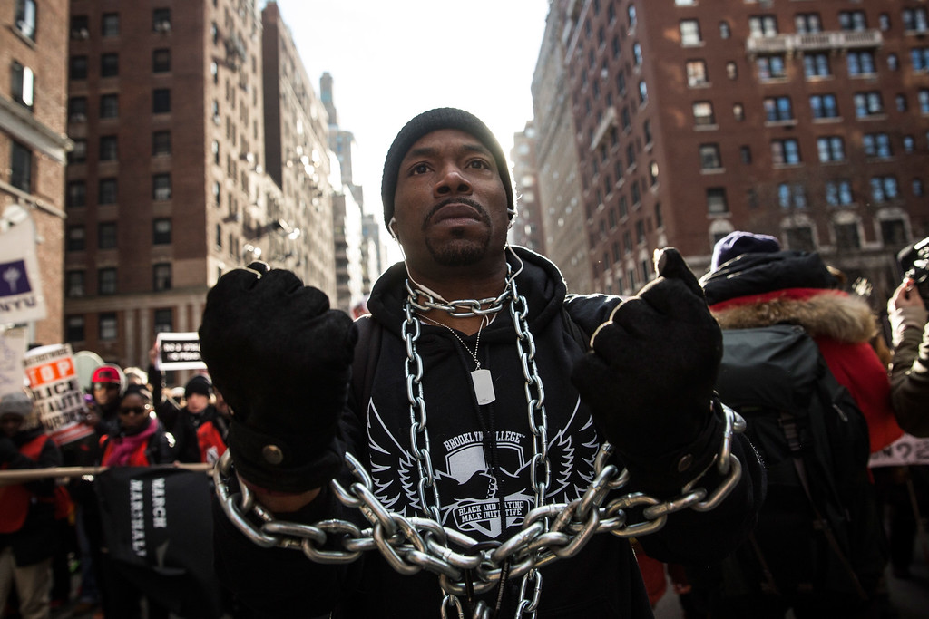 . A man is wrapped in chains as people march in the National March Against Police Violence, which was organized by National Action Network, through the streets of Manhattan on December 13, 2014 in New York City. The march coincided with a march in Washington D.C. and comes on the heels of two grand jury decisions not to indict white police officers in the deaths of two unarmed black men.  (Photo by Andrew Burton/Getty Images)