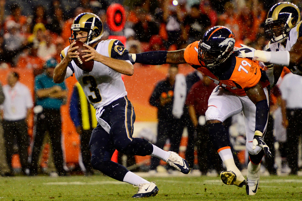 . DENVER, CO - AUGUST 24: Tim Jenkins (3) of the St. Louis Rams evades the grasp of John Youboty (79) of the Denver Broncos during the second half of the Broncos\' 27-20 preseason game win at Sports Authority Field at Mile High on August 24, 2013. This is the third game of the preseason for the Broncos. (Photo by AAron Ontiveroz/The Denver Post)