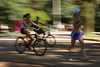 Ciclistas e corredor em movimento