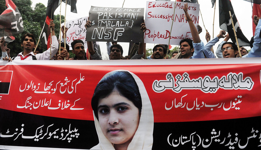""". Pakistani youths shout slogans during a protest against the assassination attempt by Taliban on child activist Malala Yousafzai in Lahore on October 15, 2012. A teenage Pakistani rights activist was flown to Britain for specialist long-term care on October 15 after being shot in the head by the Taliban for campaigning for the right to education. Malala Yousafzai, 14, who was attacked on her school bus in the former Taliban stronghold of the Swat valley last Tuesday, was sent abroad at a time when her condition is \""""optimal and before any unforeseen complications set in\"""", the military said.  Arif Ali/AFP/GettyImages"""