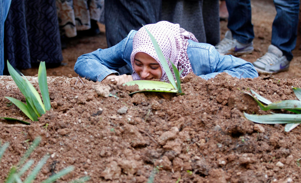 Description of . The sister of Ali Sille mourns on his grave during his funeral in the town of Reyhanli on the Turkish-Syrian border in Hatay province February 12, 2013. A Syrian minibus exploded at a crossing on Turkey's border with Syria near the Turkish town of Reyhanli on Monday, killing at least 13 people including Turkish citizens and wounding dozens more, Turkish officials said. Sille was one of the 13 victims of the explosion. REUTERS/Umit Bektas
