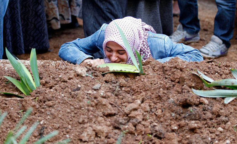 . The sister of Ali Sille mourns on his grave during his funeral in the town of Reyhanli on the Turkish-Syrian border in Hatay province February 12, 2013. A Syrian minibus exploded at a crossing on Turkey\'s border with Syria near the Turkish town of Reyhanli on Monday, killing at least 13 people including Turkish citizens and wounding dozens more, Turkish officials said. Sille was one of the 13 victims of the explosion. REUTERS/Umit Bektas