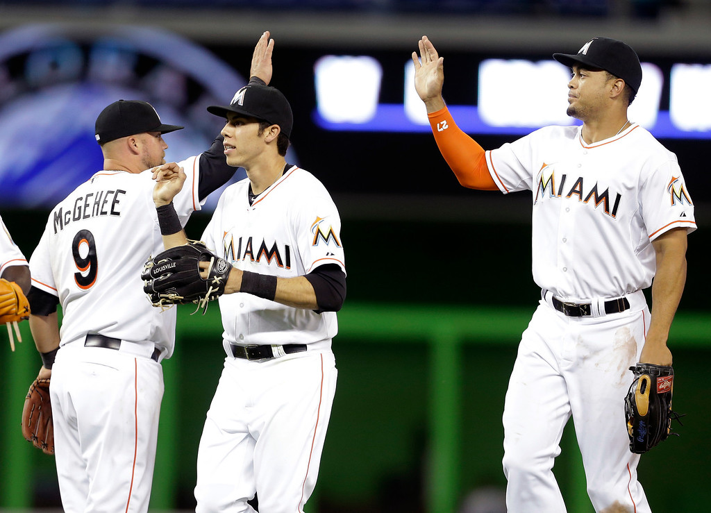 . Miami Marlins\' Casey McGehee (9), Christian Yelich, center, and Giancarlo Stanton, right, celebrate the Marlins 4-3 victory over the Colorado Rockies in a baseball game, Tuesday, April 1, 2014, in Miami. (AP Photo/Lynne Sladky)