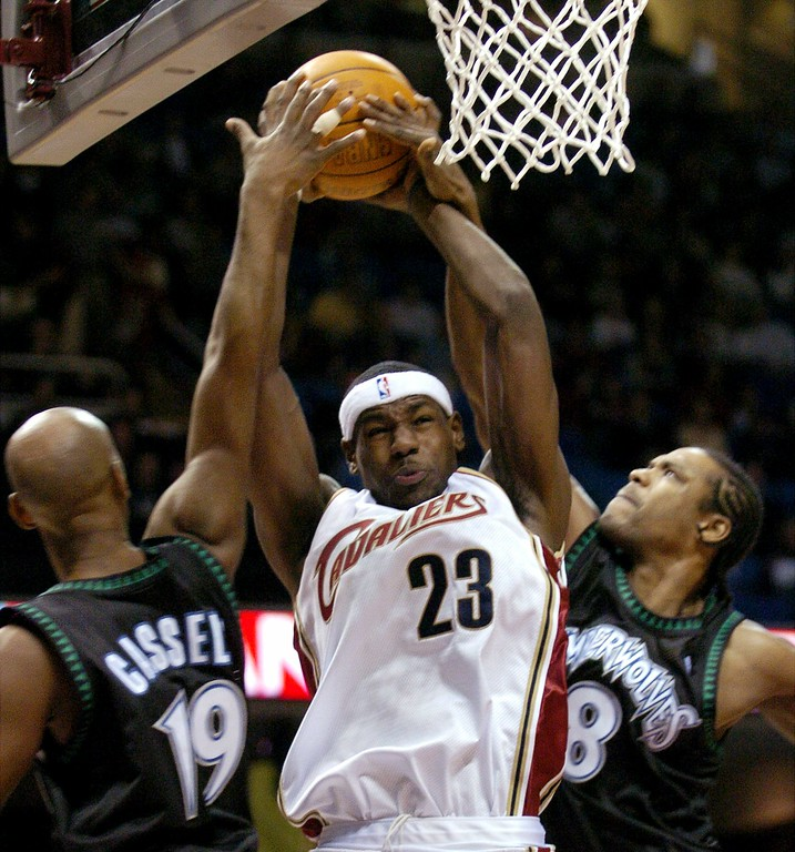 . Cleveland Cavaliers\' LeBron James (23) is stopped under the basket by Minnesota Timberwolves\' Sam Cassell (19) and Latrell Sprewell (8) during the first quarter Friday, Nov. 21, 2003, in Cleveland. (AP Photo/Tony Dejak)
