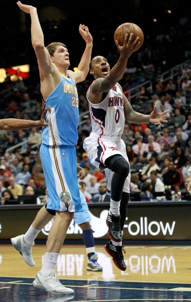 . Atlanta Hawks point guard Jeff Teague (0) drives to the basket as Denver Nuggets center Timofey Mozgov (25) defends during the first half of an NBA  basketball game on Wednesday, Dec. 5, 2012. (AP Photo/John Bazemore)