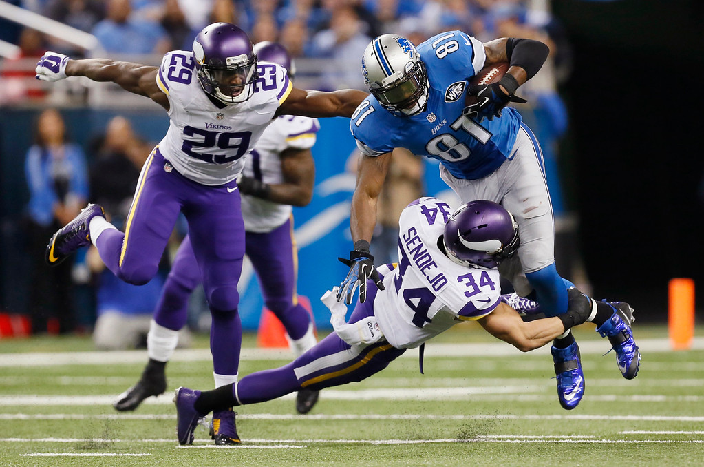 . Detroit Lions wide receiver Calvin Johnson (81) is tackled by Minnesota Vikings free safety Andrew Sendejo (34) as cornerback Xavier Rhodes (29) closes in during the second half of an NFL football game at Ford Field in Detroit, Sunday, Dec. 14, 2014. (AP Photo/Paul Sancya)