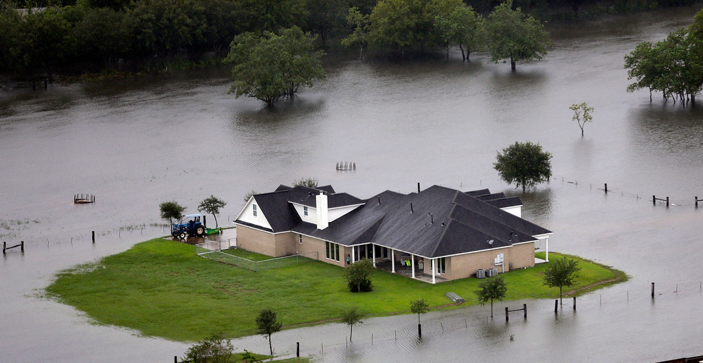 . A home is surrounded by floodwaters from Tropical Storm Harvey on Tuesday, Aug. 29, 2017, in Houston. With its flood defenses strained, the crippled city of Houston anxiously watched dams and levees Tuesday to see if they would hold until the rain stops, and meteorologists offered the first reason for hope - a forecast with less than an inch of rain and even a chance for sunshine. (AP Photo/David J. Phillip)