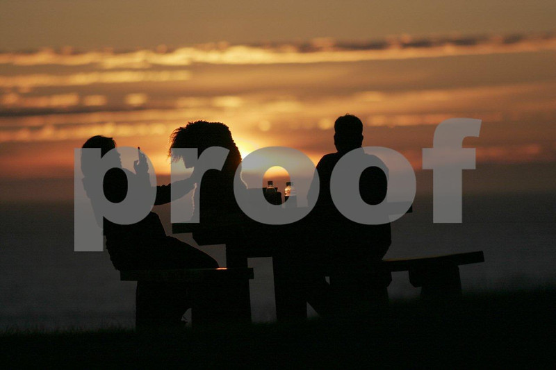 A couple at sunset sitting on a picnic table and using a cell phone to take a photo of their dog at Ecola State Park near Cannon Beach, Oregon.