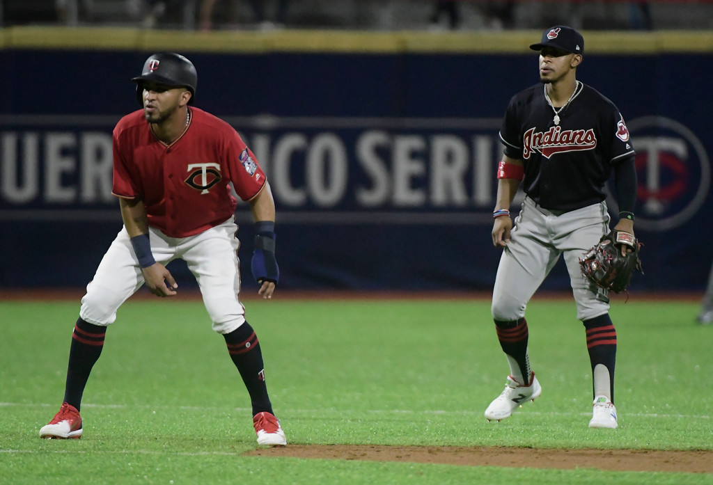 . Minnesota Twins outfielder Eddie Rosario, left, tries to steal third base as Cincinnati Indians Francisco Lindor looks on during the fourth inning of game one, of a two-game MLB Series, at Hiram Bithorn Stadium in San Juan, Puerto Rico, Tuesday, April 17, 2018. (AP Photo/Carlos Giusti)