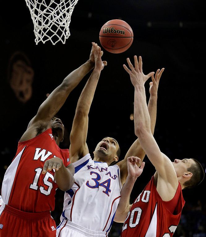 . Kansas forward Perry Ellis (34) battles Western Kentucky forward O\'Karo Akamune (15) and center Aleksejs Rostov (20) for a rebound during the second half of a second-round game of the NCAA college basketball tournament Friday, March 22, 2013, in Kansas City, Mo. Kansas won 64-57. (AP Photo/Charlie Riedel)