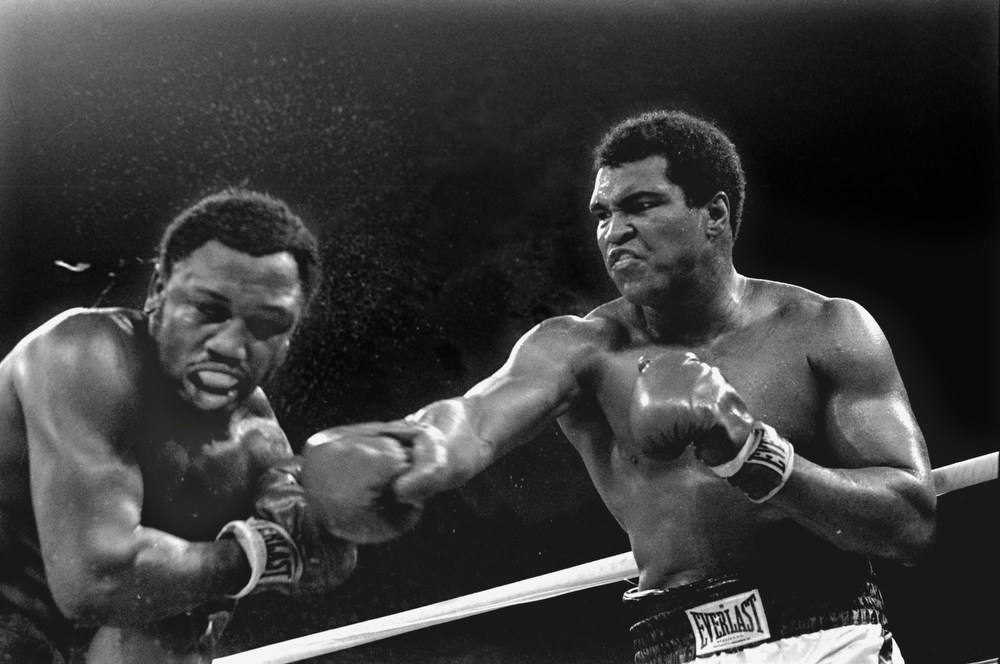 . In this Oct. 1, 1975 file photo, spray flies from the head of challenger Joe Frazier, left, as heavyweight champion Muhammad Ali connects with a right in the ninth round of their title fight in Manila, Philippines.(AP Photo/Mitsunori Chigita, File)