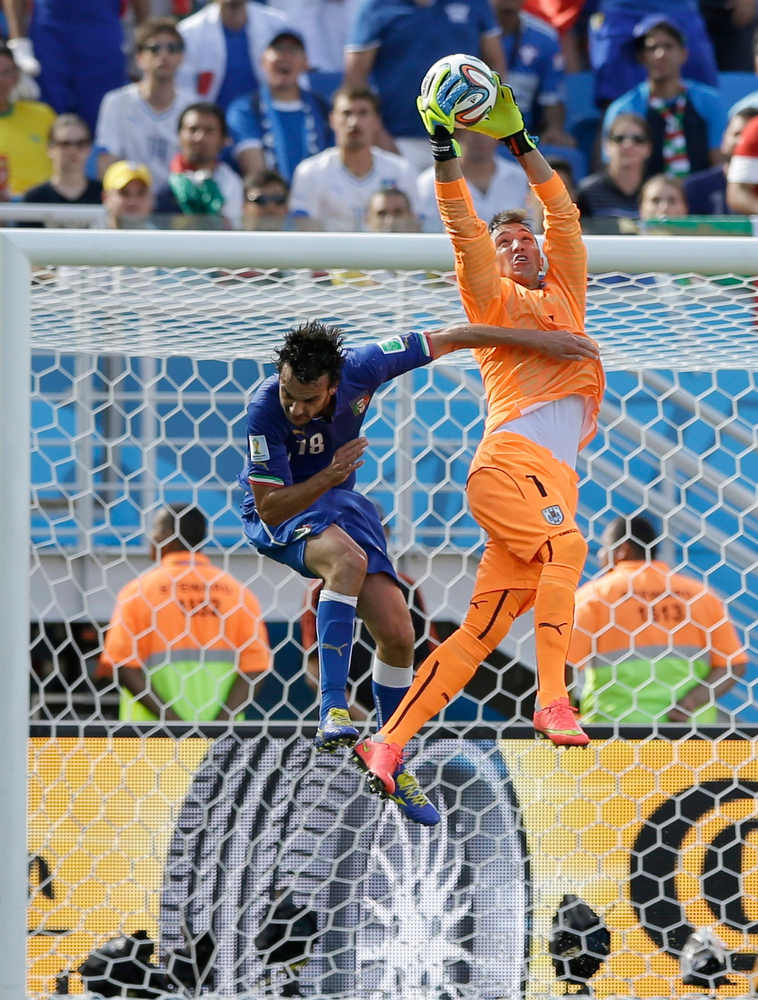 . Uruguay\'s goalkeeper Fernando Muslera makes a save over Italy\'s Marco Parolo during the group D World Cup soccer match between Italy and Uruguay at the Arena das Dunas in Natal, Brazil, Tuesday, June 24, 2014. (AP Photo/Ricardo Mazalan)