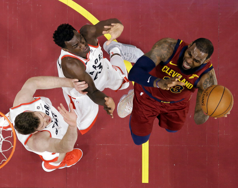 . Toronto Raptors\' Jakob Poeltl, left, and Pascal Siakam defend against Cleveland Cavaliers\' LeBron James during the first half of an NBA basketball game Wednesday, March 21, 2018, in Cleveland. (AP Photo/Tony Dejak)