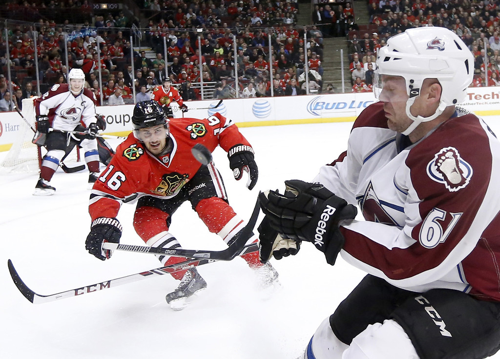 . Chicago Blackhawks center Marcus Kruger (16) and Colorado Avalanche defenseman Andre Benoit (61) battle for a loose puck during the first period of an NHL hockey game Tuesday, March 4, 2014, in Chicago. (AP Photo/Charles Rex Arbogast)