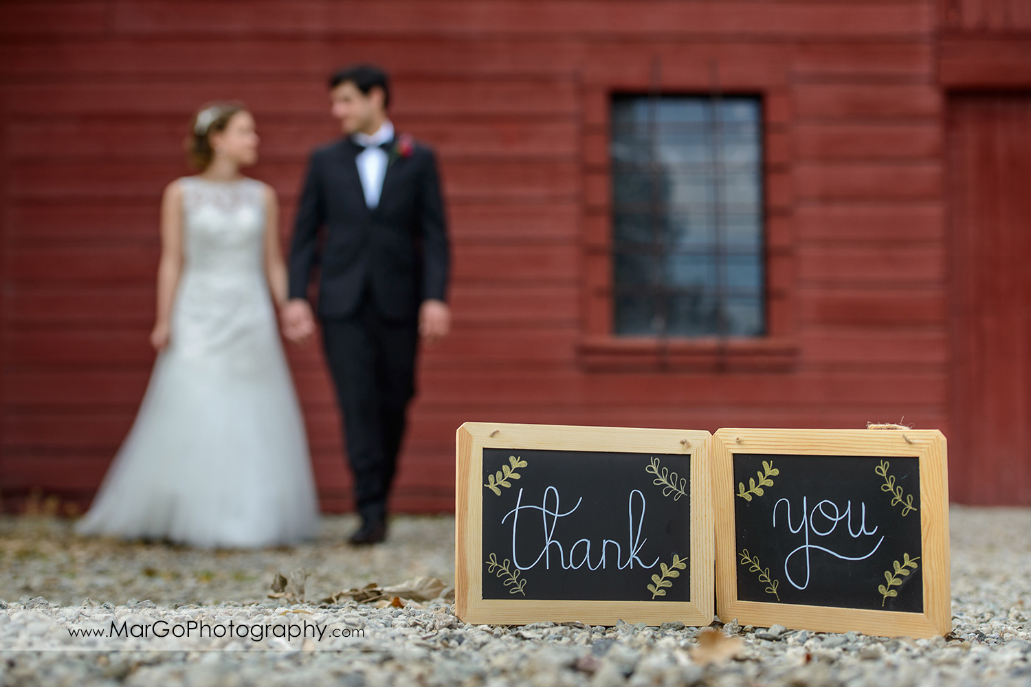 thank you signs with bride and groom at red barn wall in the background at Shinn Historical Park and Arboretum in Fremont