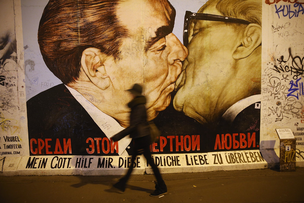 . A visitor walks past a mural showing former Soviet leader Leonid Brezhnev (L) kissing former East German communist leader Erich Honecker by Russian painter Dmitri Vrubel at the East Side Gallery, which is a 1.3 km-long original section of the Berlin Wall and is today a popular tourist attraction, on October 28, 2014 in Berlin, Germany. (Photo by Sean Gallup/Getty Images)