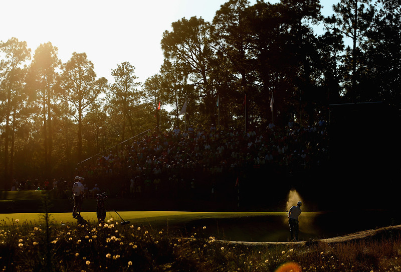 . Brandt Snedeker of the United States hits a shot from a greenside bunker on the 16th hole as Kevin Na of the United States looks on during the third round of the 114th U.S. Open at Pinehurst Resort & Country Club, Course No. 2 on June 14, 2014 in Pinehurst, North Carolina.  (Photo by Andrew Redington/Getty Images)