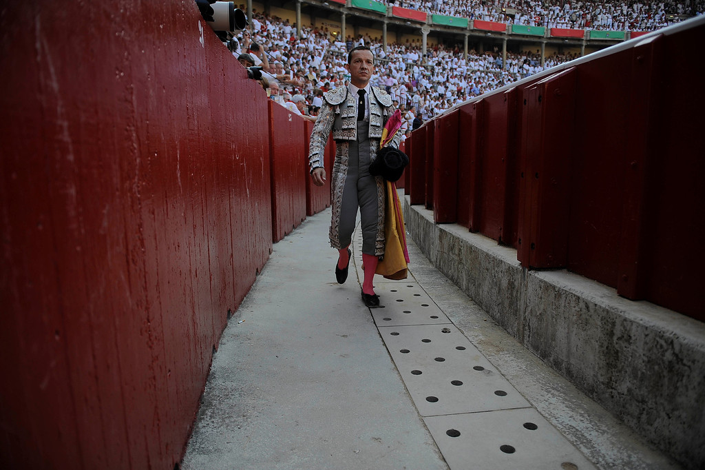 . An assistant walks around of the border of the bullring during Torrestrella\'s ranch fighting bull, at San Fermin fiestas, in Pamplona, northern Spain on Thursday, July 11, 2013. (AP Photo/Alvaro Barrientos)