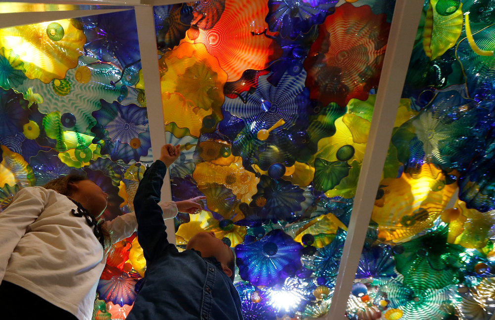 . Kristy McGuire, 8, and her brother Harry, 6, pose underneath a glass sculpture \'Persian Pergola Ceiling\' by U.S. artist Dale Chihuly during the launch of an exhibition of his work \'Dale Chihuly: Beyond the Object\' at the Halcyon Gallery in London, Tuesday, Feb. 4, 2014. (AP Photo/Sang Tan)