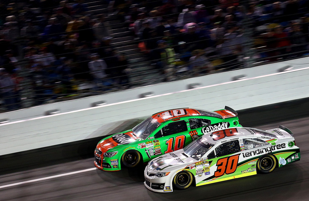 . Parker Kligerman, driver of the #30 Swan Energy Toyota, races Danica Patrick, driver of the #10 GoDaddy Chevrolet, during the NASCAR Sprint Cup Series Daytona 500 at Daytona International Speedway on February 23, 2014 in Daytona Beach, Florida.  (Photo by Tom Pennington/Getty Images)