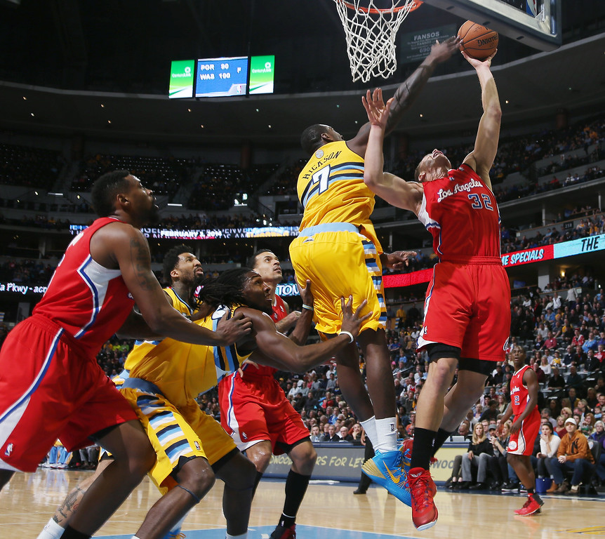 . Los Angeles Clippers forward Blake Griffin, right, goes up for a shot as Denver Nuggets forward J.J. Hickson covers in the first quarter of an NBA basketball game in Denver, Monday, Feb. 3, 2014. (AP Photo/David Zalubowski)