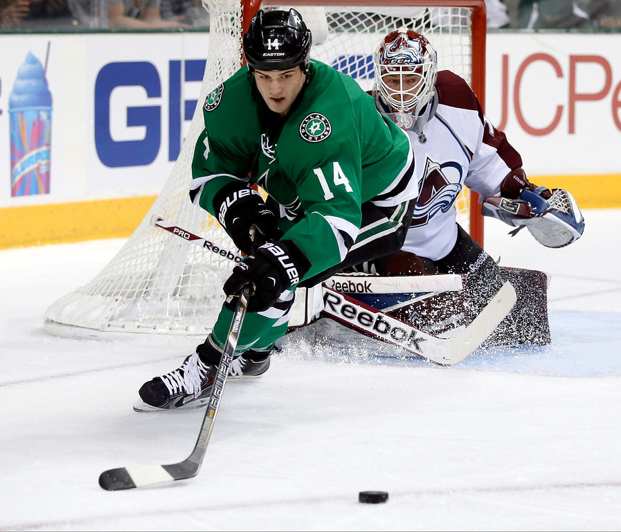 . Dallas Stars left wing Jamie Benn (14) attempts to control a puck in front of Colorado Avalanche goalie Jean-Sebastien Giguere in the first period of an NHL hockey game, Tuesday, Dec. 17, 2013, in Dallas. (AP Photo/Tony Gutierrez)