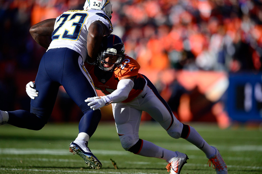 . San Diego Chargers running back Ronnie Brown (23) is tackled by Denver Broncos cornerback Chris Harris (25) in the first quarter. The Denver Broncos take on the San Diego Chargers at Sports Authority Field at Mile High in Denver on January 12, 2014. (Photo by AAron Ontiveroz/The Denver Post)