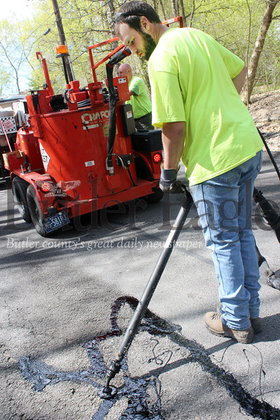 Harold Aughton/Butler Eagle: Tommy Stoughton of Butler Public Works seals the crack in the road on Pittsburgh Pike Monday morning. This preventive maintenance process keeps water from infiltrating the subsurface, while protecting the integrity and extending the life of the asphalt. According to the Public Works website, the department is responsible for the maintenance of 53 miles of city streets and 30 miles of secondary streets.