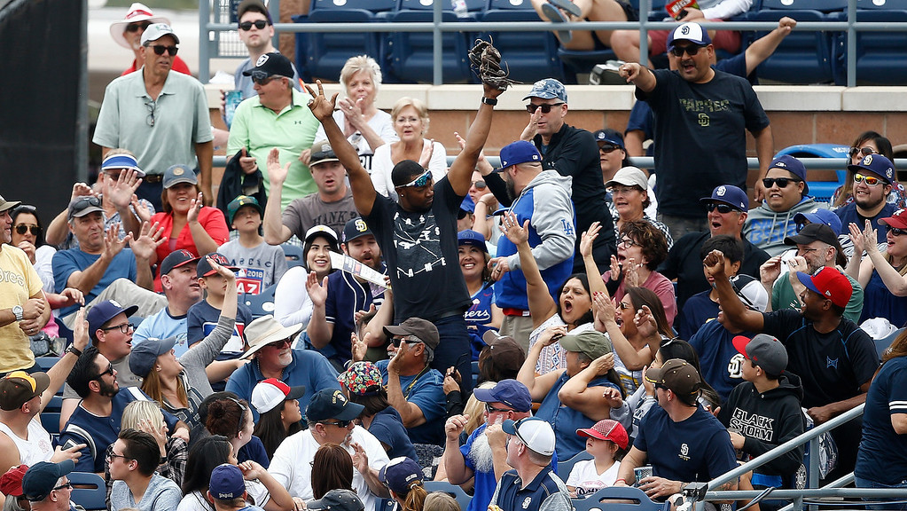 . FILE - In this March 10, 2018, file photo, a fan reacts after catching a foul ball during the third inning of a spring training baseball game between San Diego Padres and the Cleveland Indians, in Peoria, Ariz. A legend was made Tuesday, June 5, 2018, when a foul ball hit by Atlanta Braves\'  Ender Inciarte landed in Gabby DiMarco\'s full cup of beer during the fifth inning of a baseball game against the San Diego Padres, in San Diego. DiMarco then stood up and chugged her entire drink. (AP Photo/Ross D. Franklin, File)