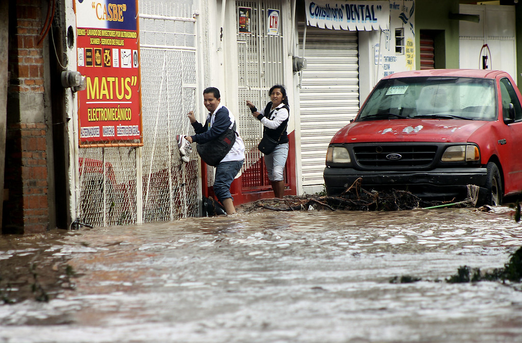 . Residents attemp to cross a flooded street in Chilpancingo, state of Guerrero, Mexico, on September 17, 2013. Mexican authorities scrambled Tuesday to launch an air lift to evacuate tens of thousands of tourists stranded amid floods in the resort of Acapulco following a pair of deadly storms. The official death toll rose to 47 after the tropical storms, Ingrid and Manuel, swarmed large swaths of the country during a three-day holiday weekend, sparking landslides and causing rivers to overflow in several states.  EDUARDO GUERRERO/AFP/Getty Images