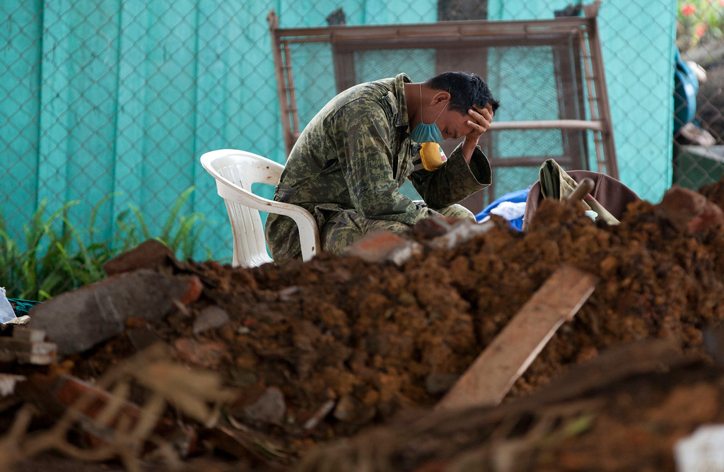 . In this Sunday, Sept. 22, 2013 photo, a soldier takes a break during the search for bodies in La Pintada, Mexico, where a landslide swept through the village center. La Pintada was the scene of the single greatest tragedy in destruction wreaked by the twin storms, Manuel and Ingrid, which simultaneously pounded both of Mexico\'s coasts a week ago, spawning huge floods and landslides across a third of the country. The death toll stands at 101, not counting five federal police who died on a rescue mission and the 68 missing from La Pintada. (AP Photo/Eduardo Verdugo)