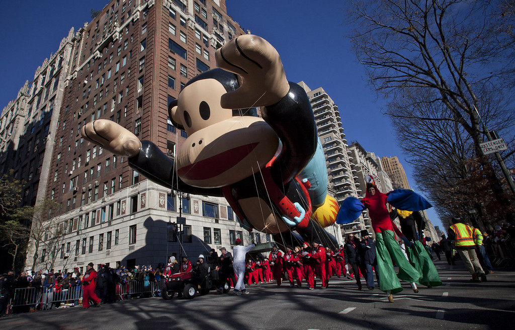 . Performers walk alongside giant floating balloons during the Macy\'s Thanksgiving Day Parade on November 28, 2013 in New York City. Despite earlier concerns about the wind, the balloons flew as planned for the parade. (Photo by Kena Betancur/Getty Images)