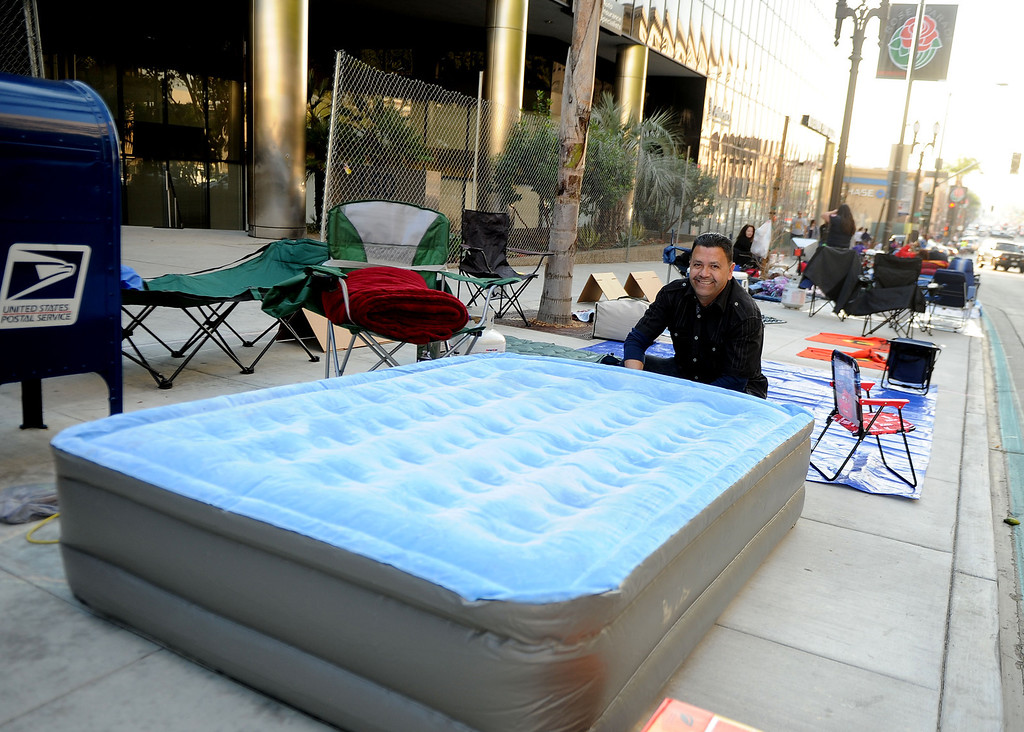. Oscar Jaime of Pasadena airs his mattress as people camp out and stake their spots for the Rose Parade along Colorado Boulevard in Pasadena, Calif., on Tuesday, Dec. 29, 2013.     (Keith Birmingham Pasadena Star-News)