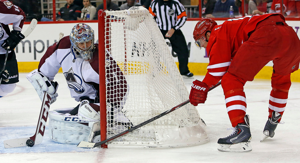 . Carolina Hurricanes\' Eric Staal, right, tries to squeeze the puck past Colorado Avalanche goalie Semyon Varlamov (1), of Russia, during the second period of an NHL hockey game in Raleigh, N.C., Tuesday, Nov. 12, 2013. (AP Photo/Karl B DeBlaker)