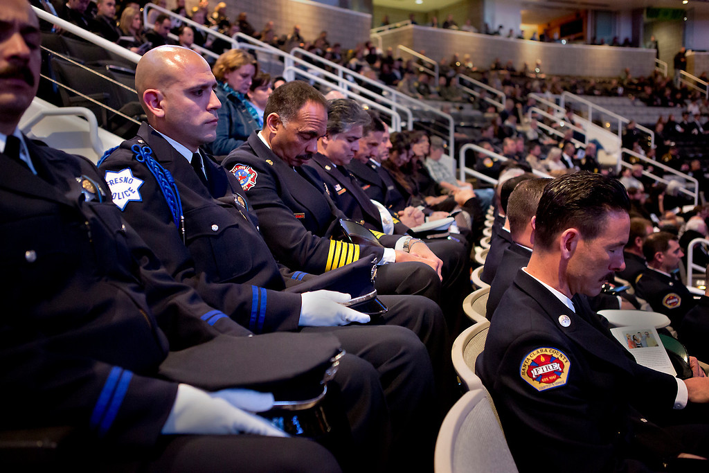 . Public officials hang their heads in prayer on Thursday morning the memorial service for detective Sgt. Loran \'Butch\' Baker and detective Elizabeth Butler at the HP Pavilion in San Jose. (Kevin Johnson/Sentinel)