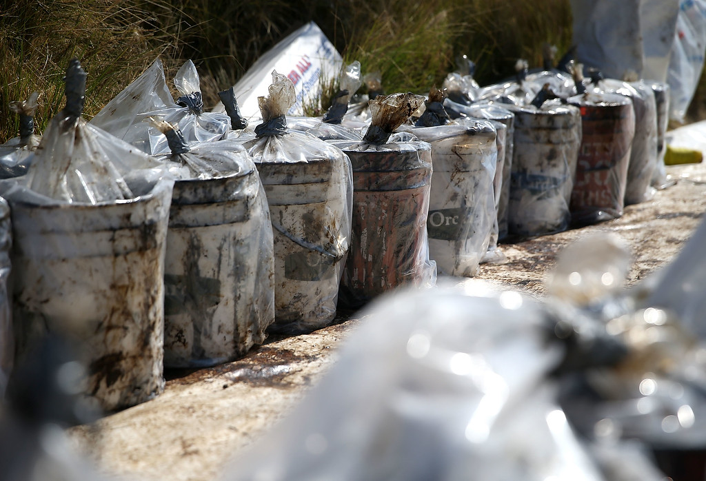. Buckets filled with oil contaminated sand are lined up during a cleanup operation near Refugio State Beach on May 22, 2015 in Goleta, California. California Gov. Jerry Brown declared a State of Emergency after over 100,000 gallons of oil spilled from an abandoned pipeline on the land near Refugio State Beach, spreading over about nine miles of beach within hours. The largest oil spill ever in U.S. waters at the time occurred in the same section of the coast in 1969 where numerous offshore oil platforms can be seen, giving birth to the modern American environmental movement. (Photo by Justin Sullivan/Getty Images)