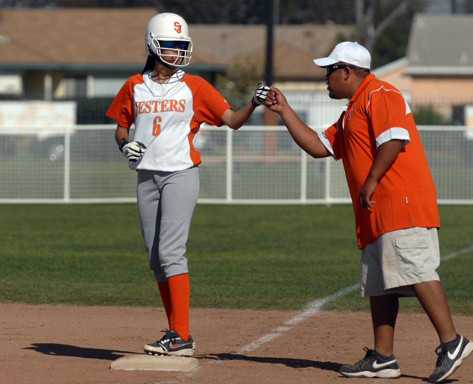 . 3/29/10 - St. Joseph\'s Yasmin Cruz gets a fist bump from her coach at first base during a game against St. Paul on Monday afternoon. The Jesters won 7-1.