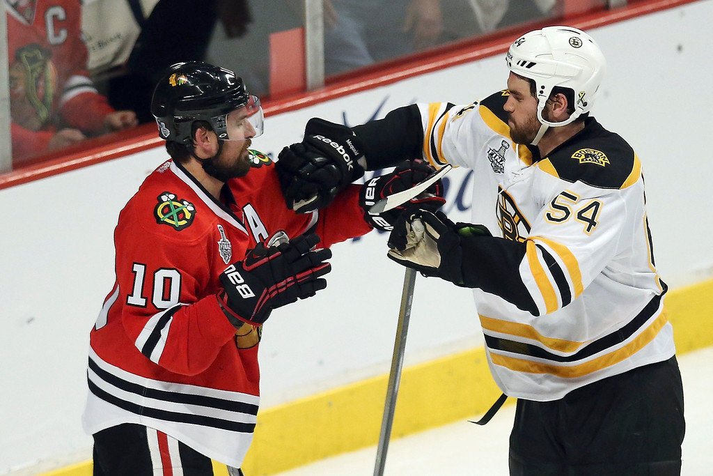 . Patrick Sharp #10 of the Chicago Blackhawks shoves Adam McQuaid #54 of the Boston Bruins in the second period in Game One of the 2013 NHL Stanley Cup Final at United Center on June 12, 2013 in Chicago, Illinois.  (Photo by Jonathan Daniel/Getty Images)