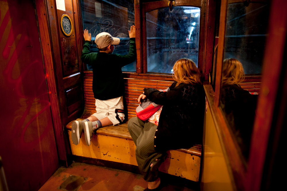 Description of . A child looks through the window of a wooden carriage car on the historic subway system, Line A, in Buenos Aires, Argentina, Wednesday, Jan. 2, 2013. The city government announced that the almost 100-year-old 'La Brugeoise