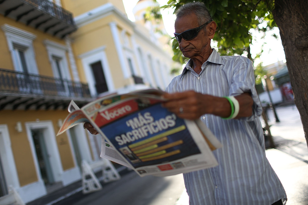 ". Jose Vasquez reads a newspaper with a Spanish headline that reads, ""more sacrifices,\"" a day after the speech Puerto Rican Governor Alejandro Garcia Padilla gave regarding the government\'s $72 billion debt on June 30, 2015 in San Juan, Puerto Rico. The Governor said in his speech that the people will have to sacrifice and share in the responsibilities for pulling the island out of debt.  (Photo by Joe Raedle/Getty Images)"