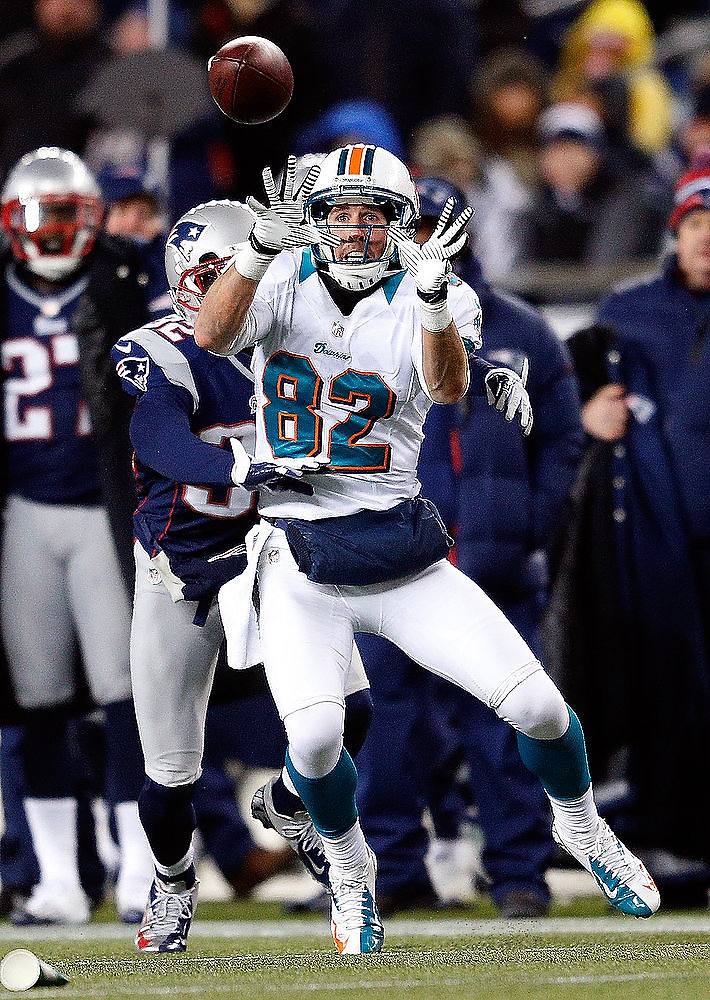 Description of . Brian Hartline #82 of the Miami Dolphins is defended by Devin McCourty #32 of the New England Patriots in the first half at Gillette Stadium on December 30, 2012 in Foxboro, Massachusetts. (Photo by Jim Rogash/Getty Images)