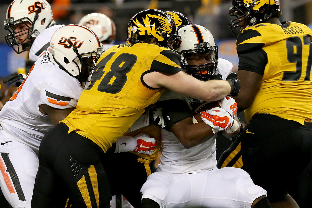 . ARLINGTON, TX - JANUARY 03:  Running back Desmond Roland #26 of the Oklahoma State Cowboys is tackled by Andrew Wilson #48 of the Missouri Tigers in the first quarter during the AT&T Cotton Bowl on January 3, 2014 in Arlington, Texas.  (Photo by Ronald Martinez/Getty Images)